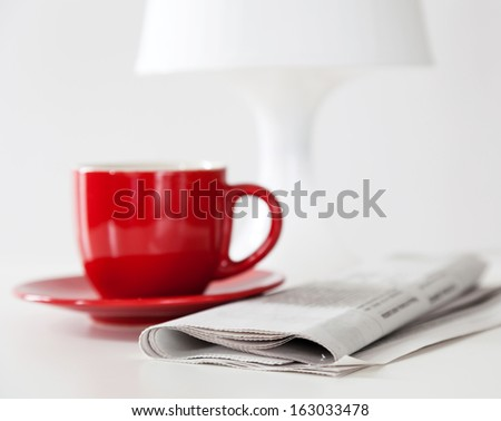 Newspaper and a coffee cup on a white table - stock photo