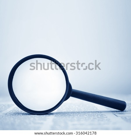 newspaper and a magnifying glass - stock photo