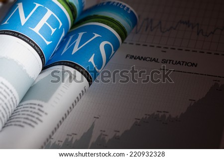 Newspaper and financial situation report with very shallow depth of field - custom designed newspaper. - stock photo