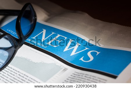 Newspaper and glasses with very shallow depth of field. - stock photo