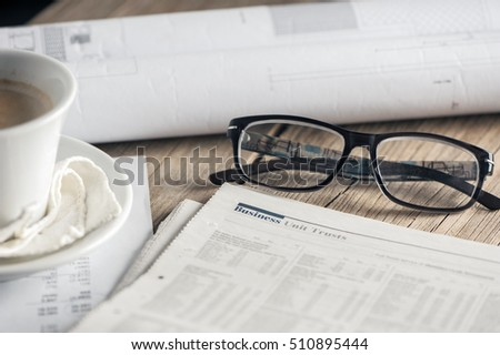 Newspaper business page with pen and cup of coffe