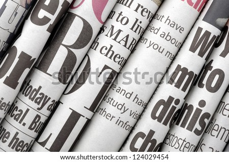 Newspaper headlines shown side on in a stack of daily newspapers - stock photo