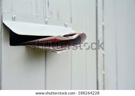 newspaper in the mail box - stock photo