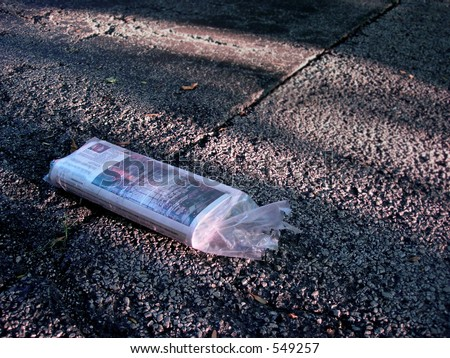 Newspaper on asphalt driveway - stock photo