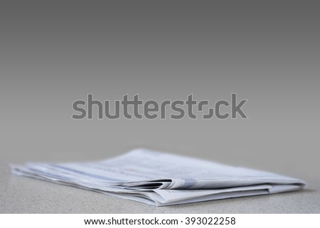 Newspaper on gray and black with shallow depth of field - stock photo