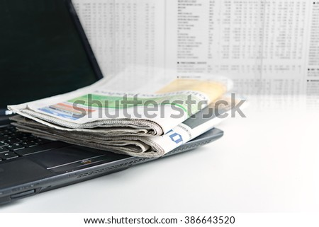 Newspaper on laptop with blurred newspaper background - stock photo