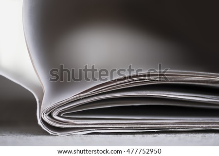 Newspaper on wooden table with shallow depth of field