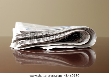 Newspaper piled on reflective desk or table - stock photo