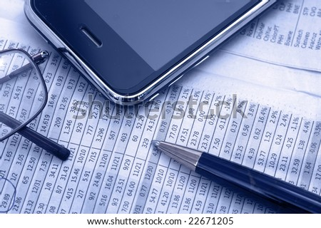 Newspaper with pda and stock charts - stock photo