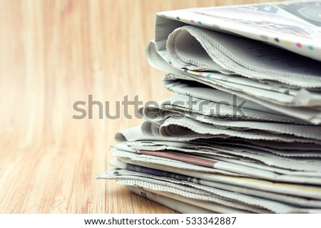 Newspaper with wooden background. Images contains grain or noise and soft focus