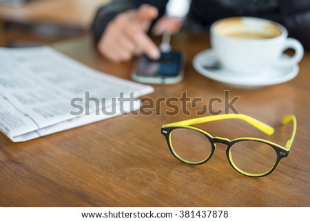 Newspapers and coffee cup, reading glasses,  hands holding tablet, cell phone. - stock photo