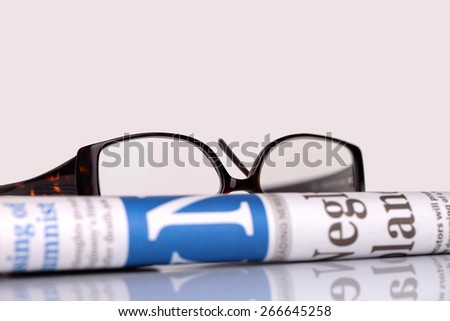 newspapers and glasses lying on table - stock photo