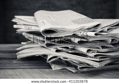 Newspapers and magazines on old wood background. Black and white shot. - stock photo