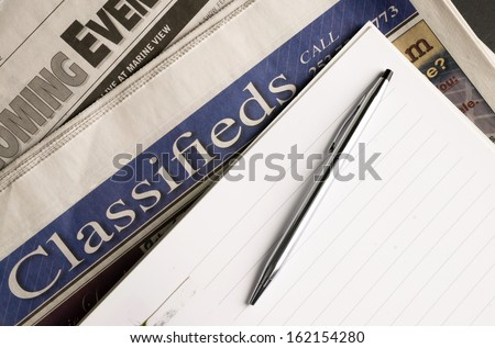 Newspapers Classified Section Coming Events Notepad Pen - stock photo