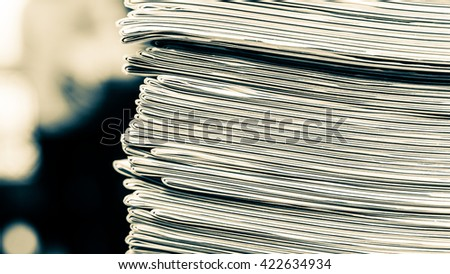 Newspapers folded and stacked concept for contact, communication, publication, Pile of newspapers shallow depth of field background image black and white horizontal photography split toning - stock photo