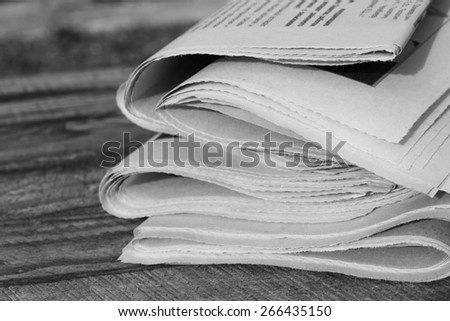 Newspapers on old wood background. Black and white shot. - stock photo