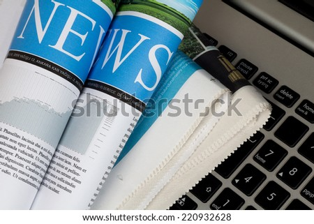 Newspapers on the keyboard of a laptop - stock photo