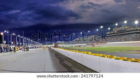 Newton Iowa, USA - June 23, 2012: Indycar Iowa Corn 250. Nightime racing action, under the lights, at Iowa Speedway. Pit lane before race, overcast threatening skies with clouds. Evening night time.