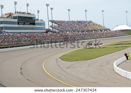 Newton Iowa, USA - June 23, 2013: Indycar Iowa Corn 250 pre-race and gridding cars, Iowa Speedway. The grandstand is full and people eagerly await the start of the race. - stock photo