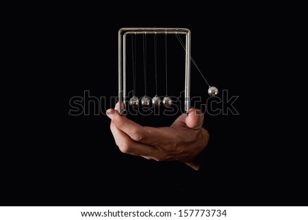 Newton's pendulum or cradle in human hands on dark background - stock photo