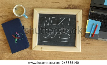 Next job written on a chalkboard at the office - stock photo