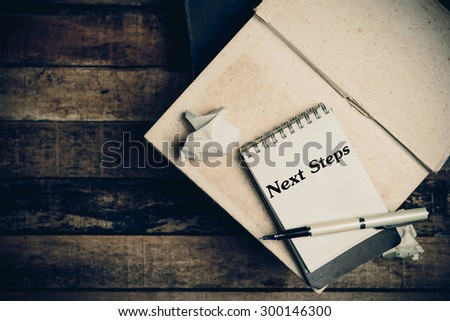 Next Steps on pages sketch book on wood table vertical  - stock photo
