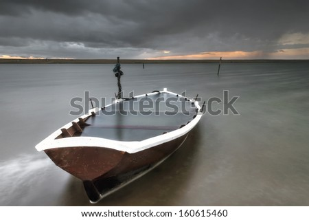 Next to the old jetty located on chesil beach, this boat has seen better days and sits, flooded with stagnating water at the sun sets behind the chesil bank just west of Weymouth.. - stock photo