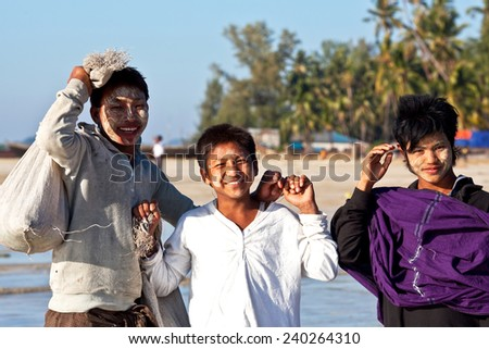 NGAPALI, RAKHAIN STATE, BURMA - JANUARY 23: Young laughing fishermen with thanaka paste on their faces poses for a photo during the Hta-Mane Festival on January 23, 2011 in Ngapali, Burma - stock photo