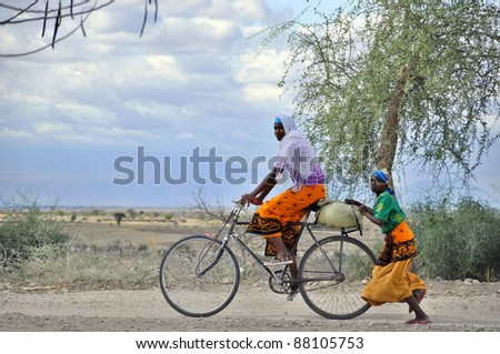 NGOROGORO -TANZANIA, OCTOBER 17: Masai woman biking and walking  through the savanna October 17 Ngorogoro, Tanzania. The Maasai are a Nilotic group in East Africa, next to the Indian Ocean. - stock photo