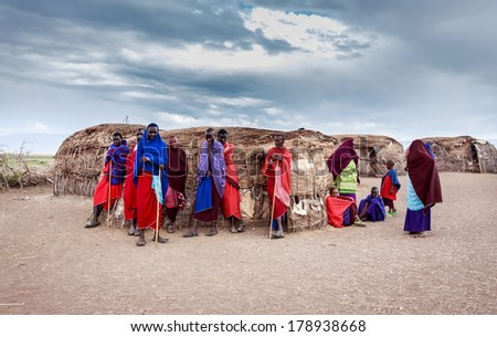 NGORONGORO, TANZANIA - DECEMBER 29, 2013 :A group of  Masai stand and relax near their house that made with cow dung and wood