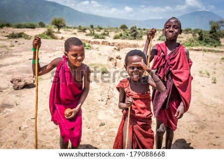NGORONGORO, TANZANIA - December 31, 2013 : Maasai unidentified children in traditional dress smile with happiness when I told them to act for the pictures taking  on December 31, 2013 in NGORONGORO, TANZANIA.  - stock photo