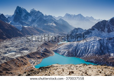Ngozumpa Glacier flowing down from the high snow capped mountains of the Himalayas. Early morning. View from Gokyo Ri - stock photo