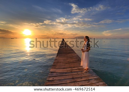 Nha Trang city, Vietnam - July 31, 2016: beautiful woman feels relaxing at pier when the sun rises