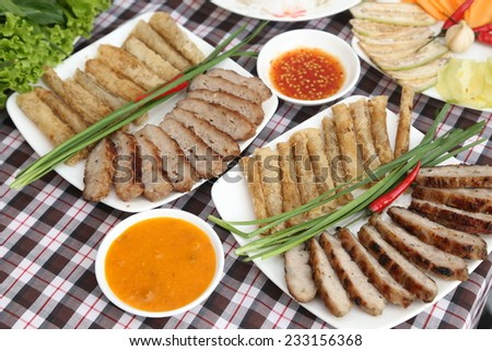 Nha Trang grilled pork sausage/ Chargrilled pork sausage skewers (Nem nuong), Vietnamese Cuisine. Sausage on chopstick are wraped in rice paper with mixed herbs. Serve with hoisin dipping sauce.  - stock photo
