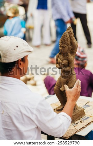 Nha Trang, VIETNAM - CIRCA February 2015 - unidentified vietnamese sculptor man with clay and figure on lunar new year. - stock photo