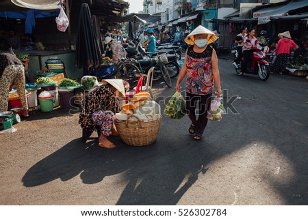 Nha Trang, Vietnam - July 14, 2016: Vietnamese woman in conical hat walks at the morning market in Nha Trang, Vietnam on July 14, 2016.