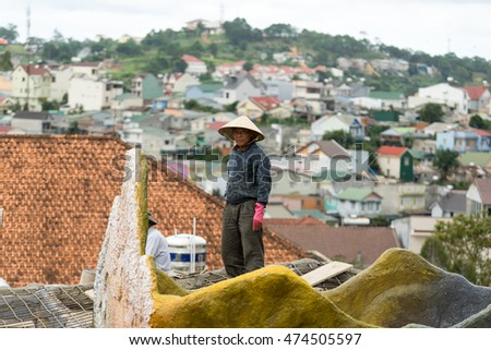 NHA TRANG, VIETNAM - JUNE 23, 2016: Asian man is standing on a roof on the background of cityscape in Vietnam