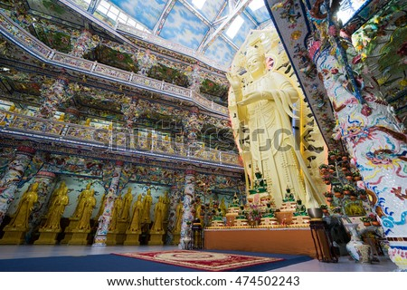 NHA TRANG, VIETNAM - JUNE 23, 2016: Big gold statue of Buddha in the temple. Internal furniture of the Buddhist church. Walls are painted with multi-colored drawings.
