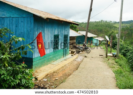 NHA TRANG, VIETNAM - JUNE 23, 2016: Small wooden house with flag in a village of tropical jungle. In the yard there is a motorcycle and nobody's around