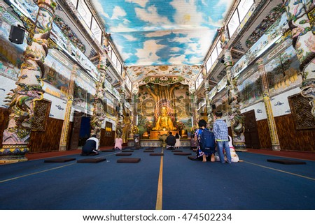 NHA TRANG, VIETNAM - JUNE 23, 2016: View of the Buddhist temple. Walls are laid out by a color mosaic. In the middle there is big gold statue of Buddha.
