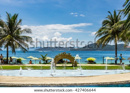 NHA TRANG , VIETNAM MAY 23 2016 : white sand beach resort with two sunbeds and umbrella with stormy sky, holiday resort in Vietnam, Hon Tam beach