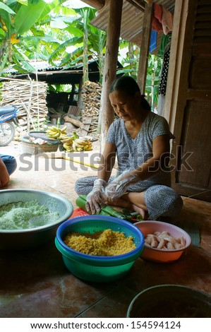 NHON TRACH, VIET NAM- JANUARY 20. Women wrap up Cylindric glutinous rice cake (banh tet) for Viet Nam Tet, it make by glutinous rice filled with green bean paste and fat pork. January 20, 2013
