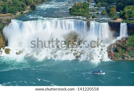 Niagara Falls closeup panorama in the day over river with rocks and boat - stock photo