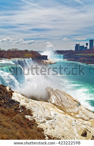 Niagara Falls from an American side and Skyscrapers in Canada. A view on American Falls, Bridal Veil Falls, Goat Island, Horseshoe falls and Canada Skyscrapers on the background.