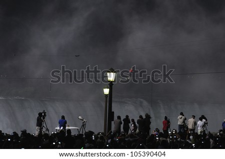 NIAGARA FALLS -JUNE 15: People waiting anxiously on the Canadian side while Nik Wallanda is crossing  the Niagara Falls on a tightrope on June 15 2012 in Niagara Falls, Canada. - stock photo