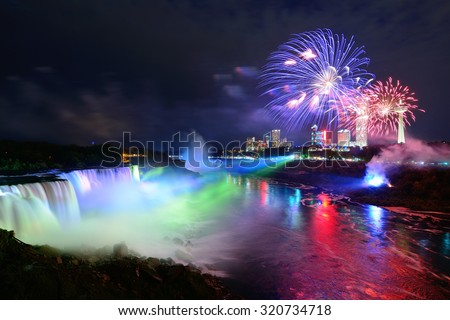 Niagara Falls lit at night by colorful lights with fireworks - stock photo