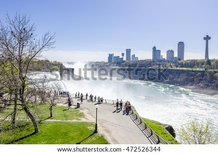 Niagara Falls, NY, USA - May 5, 2013: Visitors watching  Horseshoe Falls on sunny day at the USA side.