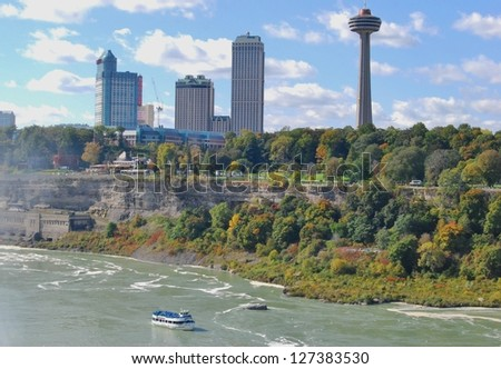 NIAGARA FALLS - OCTOBER 11: Skylon Tower, and Maid of the Mist boat tour on October 11, 2009 in Niagara Falls, Canada. Skylon Tower is at Niagara Falls, Canada, and towering 775 feet above the Falls - stock photo
