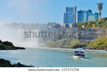 NIAGARA FALLS - OCTOBER 11: Skylon Tower, and Maid of the Mist boat tour on October 11, 2009 in Niagara Falls, Canada. Skylon Tower is at Niagara Falls, Canada, and towering 775 feet above the Falls. - stock photo