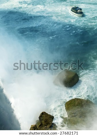 niagara horseshoe waterfalls, boat with tourists, rocks at the bottom - stock photo